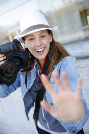 Cheerful photographer showing hand towards camera photo