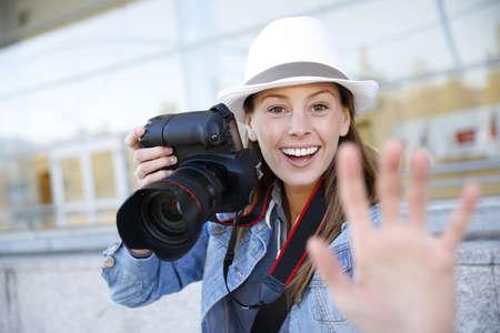 apprenticeship: Cheerful photographer showing hand towards camera