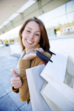 Cheerful girl in town holding shopping bags Stock Photo - 16397272