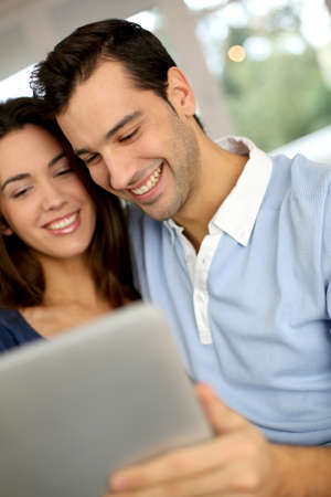 Smiling couple websurfing on internet with tablet photo