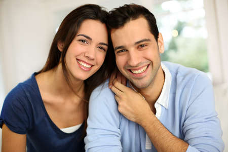 adult couple: Portrait of cute young couple sitting in sofa Stock Photo