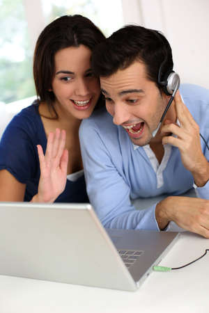 Cheerful young couple chating on internet with webcamera photo
