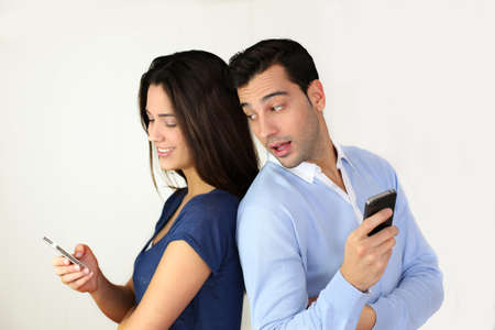 Couple standing back to back and using smartphone photo