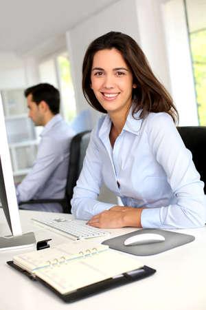 desktop computer: Smiling office worker in front of desktop computer