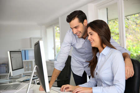 internship: Young office workers in front of desktop computer Stock Photo