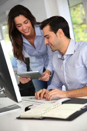 apprenticeship: Office workers in front of desktop computer with tablet Stock Photo