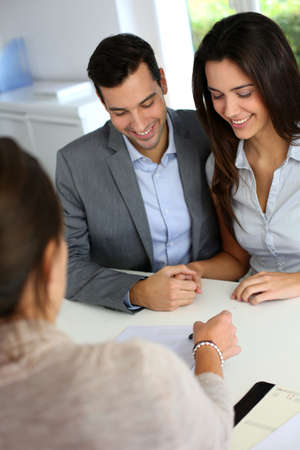 Young couple signing financial contract photo