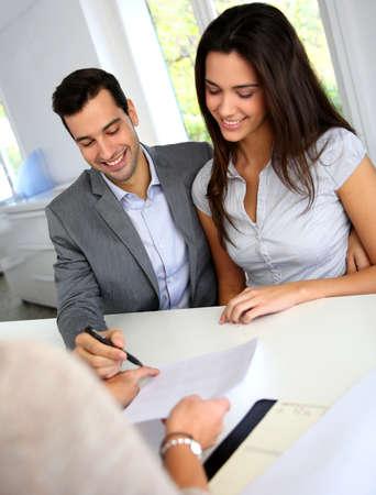 firmando: Pareja joven firma contrato financiero