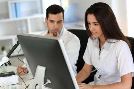 investigador cientifico: Los estudiantes que trabajan en la computadora de escritorio en el laboratorio