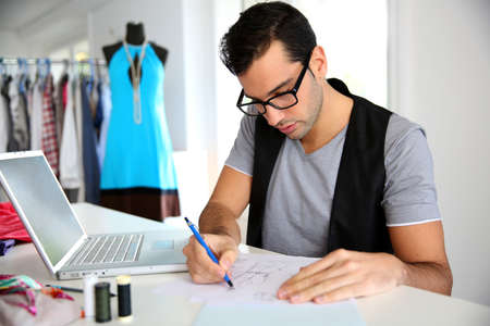 designer clothes: Smiling fashion designer in workshop