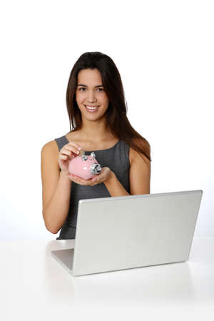 Smiling girl inserting coing in piggy bank Stock Photo - 16545815