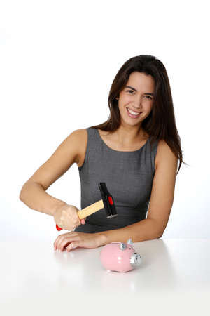 Young woman ready to break piggy bank with hammer photo