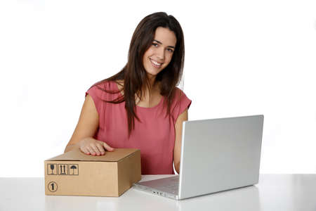 sent: Young smiling woman preparing package to be sent by mail Stock Photo