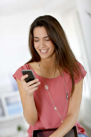 Beautiful young woman sending message with smartphone photo