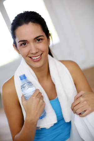 Young woman drinking water after exercising photo