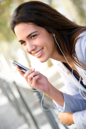 Young woman in town talking with handsfree Stock Photo - 16545680