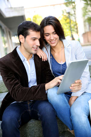 websurfing: Young couple websurfing on internet with tablet in town Stock Photo