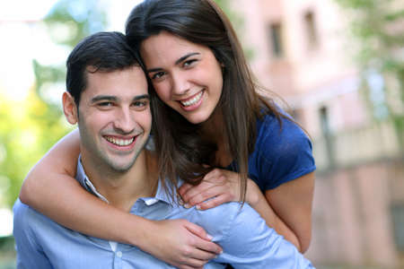 Cheerful young man carrying girlfriend on his back photo