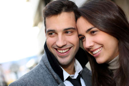 young couple smiling: Portrait of trendy couple in town