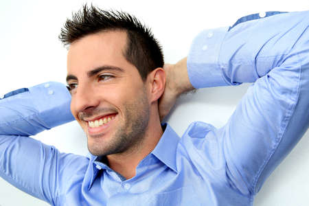 Cheerful man with stretched arms behind head photo
