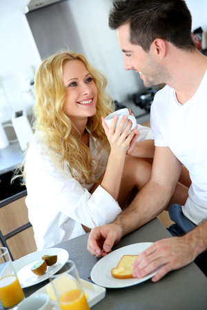 Young couple having breakfast in home kitchen Stock Photo - 16949295