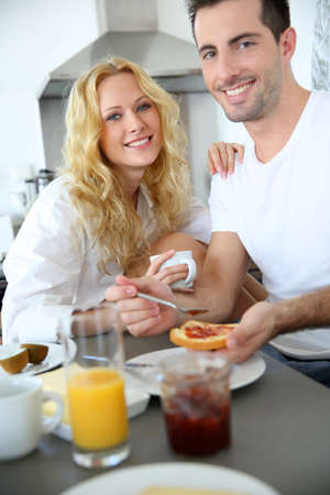 Young couple having breakfast in home kitchen photo