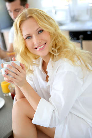 Beautiful blond girl drinking coffee for breakfast photo