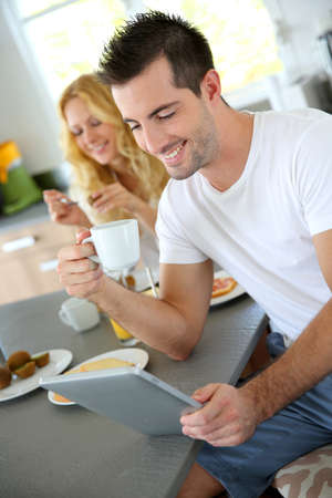 Young man sitting in home kitchen with tablet photo