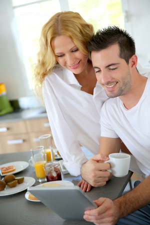 websurfing: Young couple using digital tablet at breakfast time