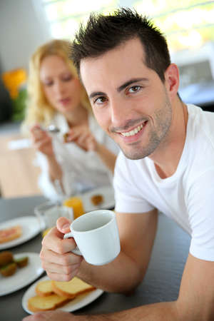 women holding cup: Portrait of young man holding cup of coffee Stock Photo