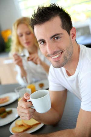 hombre tomando cafe: Retrato de hombre joven que sostiene la taza de caf�