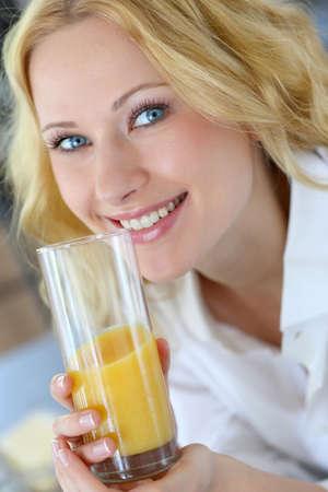 bodycare: Smiling blond woman drinking orange juice