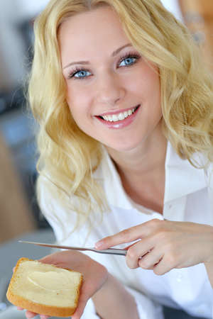 butter: Beautiful girl eating toasted bread for breakfast Stock Photo