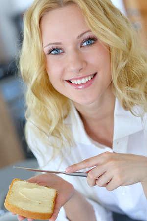 mantequilla: Hermosa niña comiendo pan tostado para el desayuno Foto de archivo