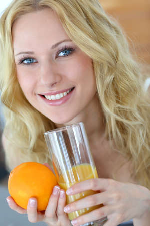 Smiling blond woman drinking orange juice photo