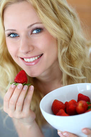 bodycare: Attractive blong girl eating strawberries