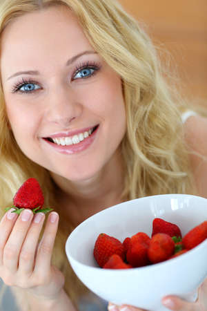 Attractive blong girl eating strawberries photo