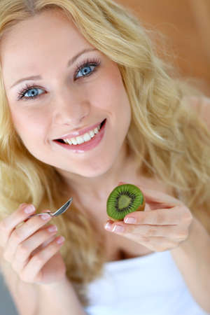 Portrait of beautiful girl eating kiwi photo
