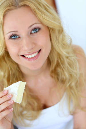Attractive girl holding slice of french cheese photo