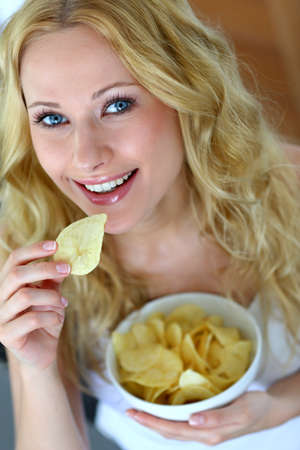 unhealthy diet: Smiling woman eating potato chips