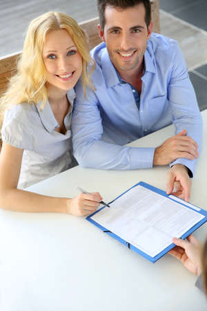 realestate: Cheerful couple signing property contract with real-estate agent