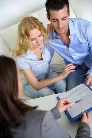 Cheerful couple signing property contract with real-estate agent photo