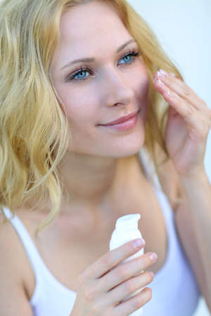 Portrait of beautiful woman applying moisturizer  Stock Photo - 16949310