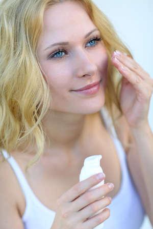 rubia ojos azules: Retrato de la hermosa mujer de aplicar la crema hidratante Foto de archivo