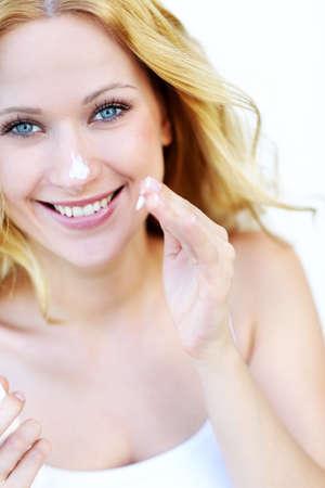 sunscreen: Portrait of beautiful woman applying moisturizer