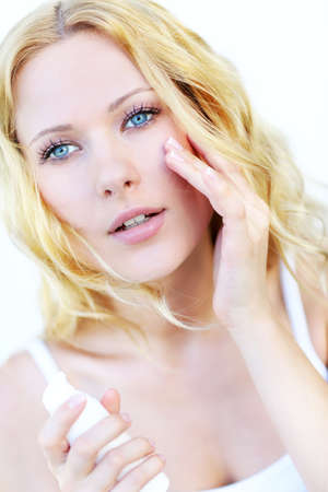 Portrait of beautiful woman applying moisturizer  photo