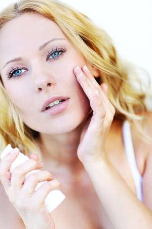 Portrait of beautiful woman applying moisturizer Stock Photo - 16949352