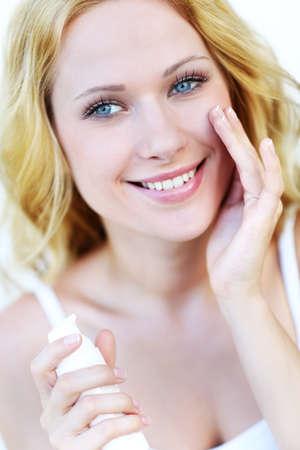 Portrait of beautiful woman applying moisturizer Stock Photo - 16949346