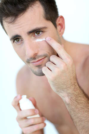 concealer: Handsome guy applying concealer around his eyes