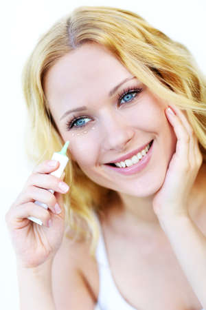 concealer: Smiling woman applying concealer in front of mirror Stock Photo